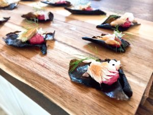 squid ink crisp topped with beetroot hummus, smoked mackerel, and fennel